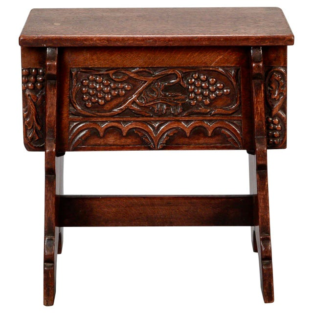 Circa 1920s French oak stool with trestle style base and carved grape details along apron. Excellent antique condition...