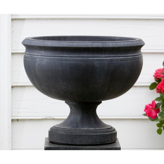 An urn planter on a pedestal in a Nero Novo finish