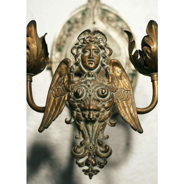 Etruscan style brass wall sconce. This cherubic centerpiece is flanked by two floral scalloped arms and is cast with a...