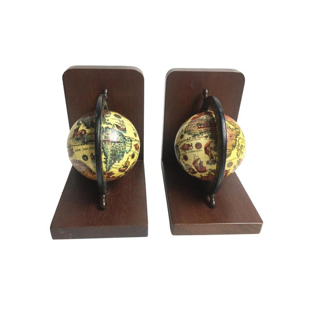 Vintage midcentury pair of wooden old world globe book ends. They are made of solid wood and stained in a deep brown color...