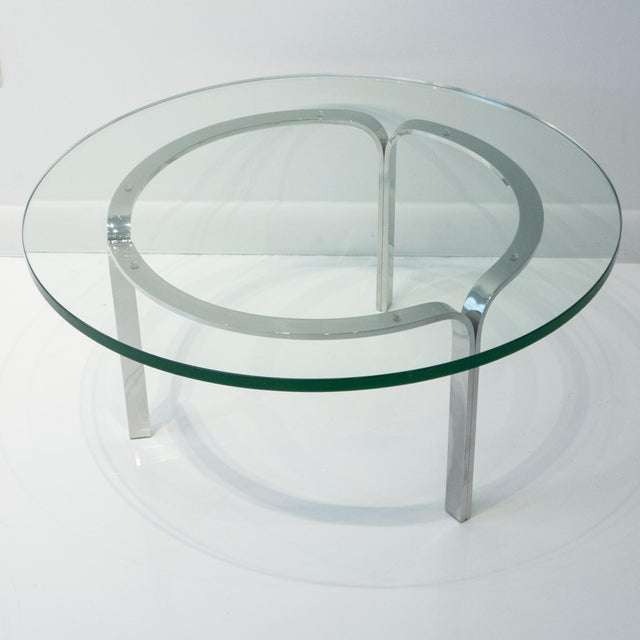 Cocktail table of polished stainless steel with a glass top. A 1960 Nicos Zographos design produced by Zographos Designs,...