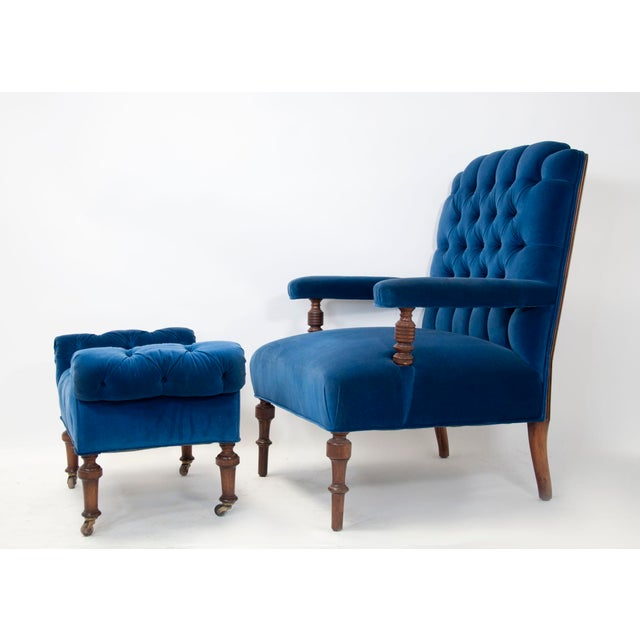 Period late Victorian, early Edwardian tufted lounge chair and ottoman, upholstered in a blue velvet. Lovely walnut turned...