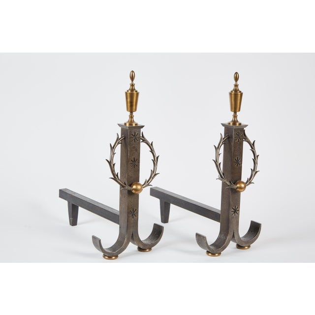 A handsome pair of late 19th-early 20th century wrought iron andirons by Samuel Yellin. The two feature finials on each...