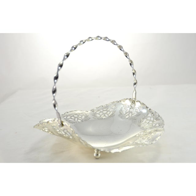 An ornate silver plate footed basket catchall with beautiful cut-work, scalloped rim and a hinged twisted handle. No...