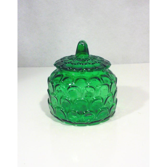 Italian emerald green glass canister style jar with a textured exterior resembling fish scales. The lid has a finial...