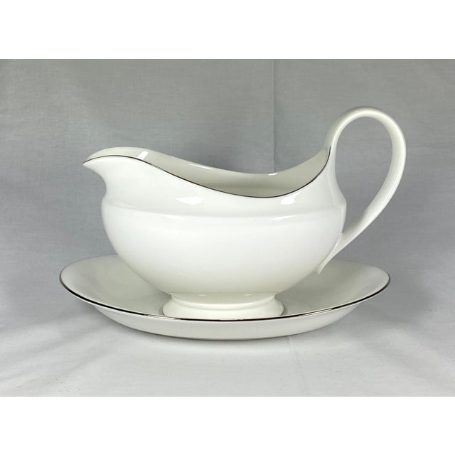 White Wedgwood gravy boat and saucer with silver gilding. Saucer measures 8.5''L x 5''W x 1.37''H.