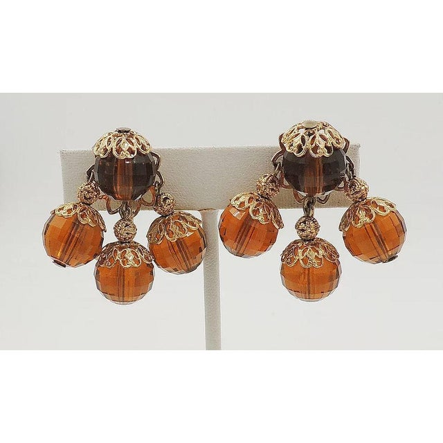 """1950s goldtone and faceted brown Lucite beads clip back earrings. Marked """"Napier."""" Measure: 1.5 inches L x 1.38 inches W...."""