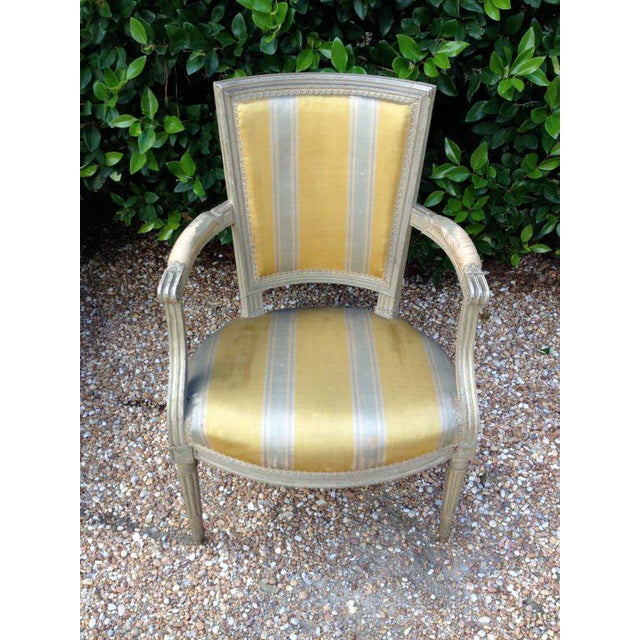 Six French Empire-style armchairs with painted grey finish distressed by age, fluted legs, straight square backs. Seat is...