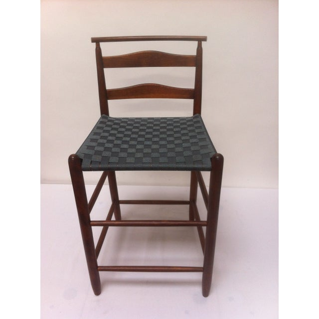 A Mid-Century Modern wooden bar height chair. The seat was redone in charcoal gray, non-elastic webbing.