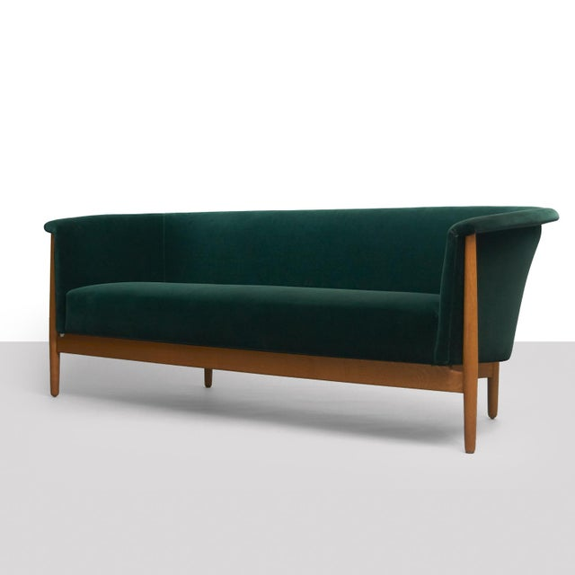 An rare and elegant sofa with rounded corners in oak with a rich natural patina. Restored in a luxurious emerald green...