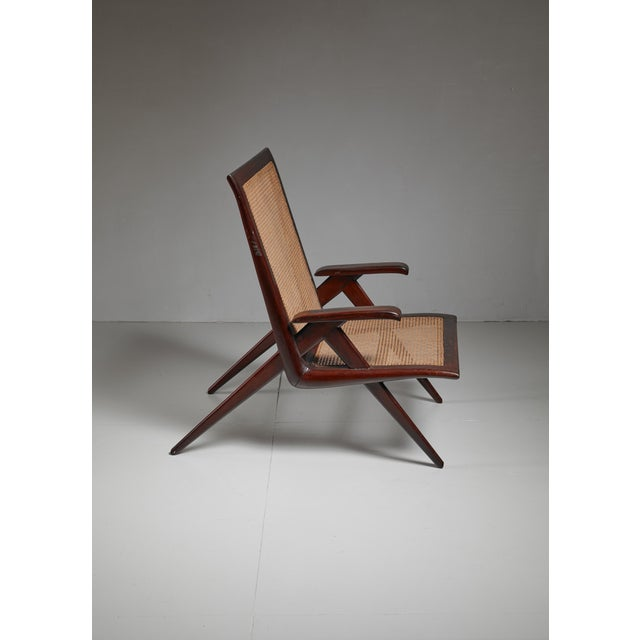 A Brazilian walnut armchair with a seating and backrest of woven cane.
