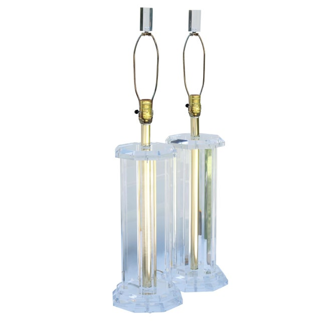 A pair of mid century modern lucite table lamps with octagonal bases. Brass plated columns are framed with four open...