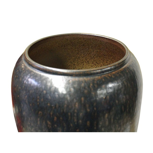 This is a handmade Chinese oriental modern ceramic tall slim vase with metallic black base color and splash marks pattern...