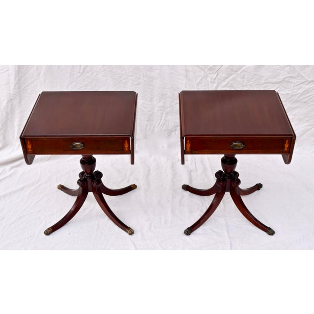 Pair of mahogany pedestal Pembroke tables. Each features one dovetailed drawer adorned on either side with neoclassical-...