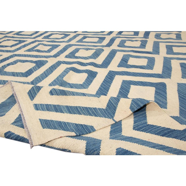 Beautiful hand-knotted modern Kilim rug with an ivory field, and blue accents an allover geometric design. This rug...