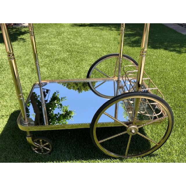 Mid Century 1970's French Brass and Mirrored Bar Cart that is Sleek, Chic and Easy on the Eyes. This Bar cart truly makes...