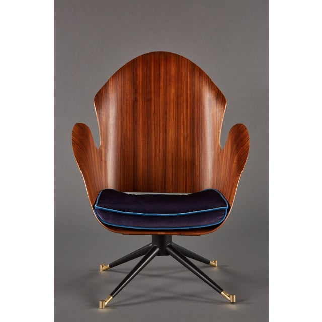A rare and sculptural pair of Mid-Century Italian swivel chairs made of shaped fruitwood, above steel and brass legs.