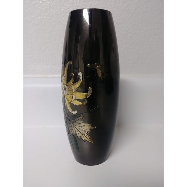 This Japanese Mixed Metal Vase of bronze, etched silver and gold accents depicts a flower, leaves, dark green stems and a...