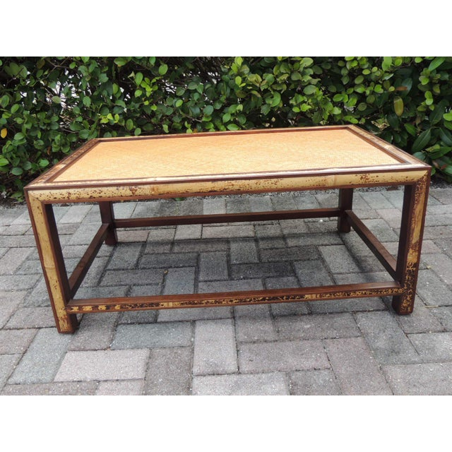 Faux tortoise bamboo and rattan coffee table. Rectangular table with rattan woven chevron pattern top. Wood frame encased...