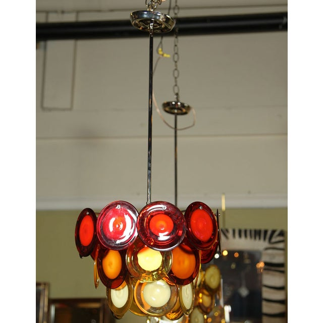 Very colorful 3 tier chandelier on chrome stem. Multi-color murano discs in shades of orange, yellow and white.