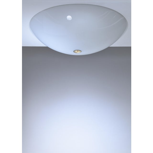 A large model 71-002 flush mount ceiling lamp for Orno. The lamp is made of a curved opaline glass shade, fixed with a...