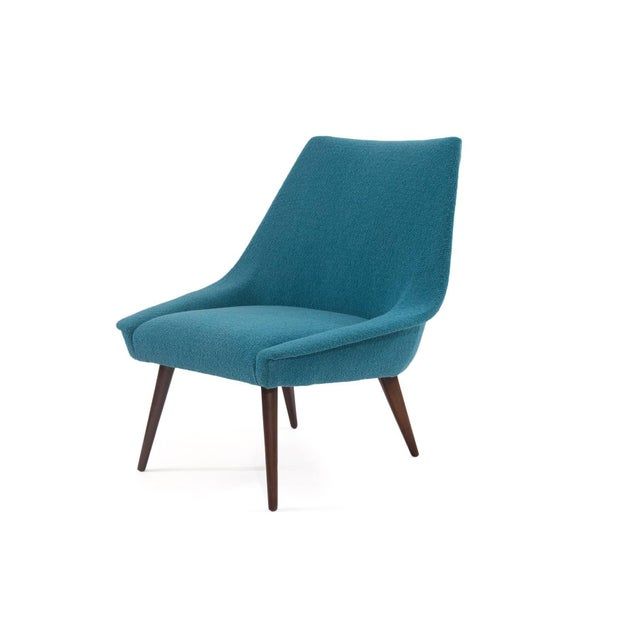 Pair of sculptural upholstered lounge chairs, circa late 1950s. These lovely examples have splayed newly finished solid...
