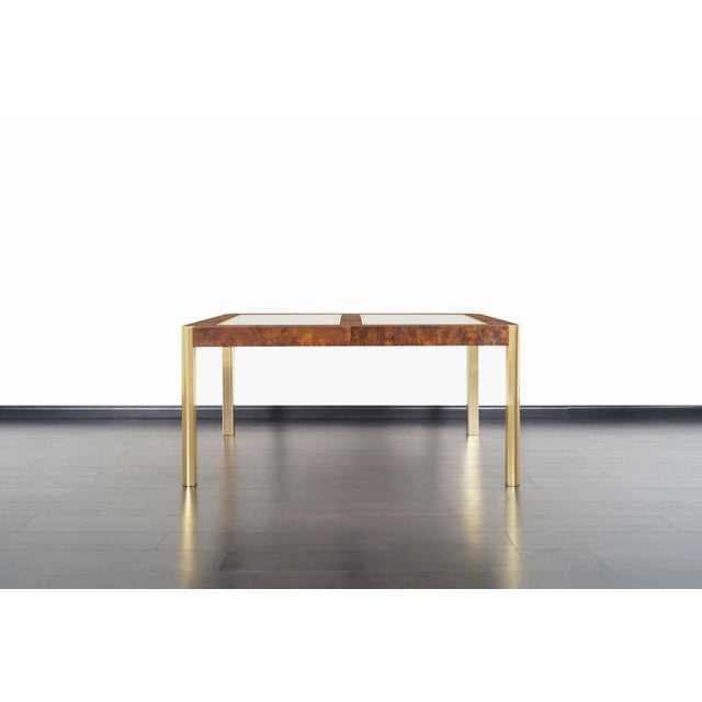 An expanding vintage burl wood and brass dining table manufactured by Century Furniture Company in the United States,...