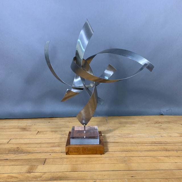 Abstract and playful, sculpture made from four steel ribbon pieces reaching upward. Two-part base of a lucite block...