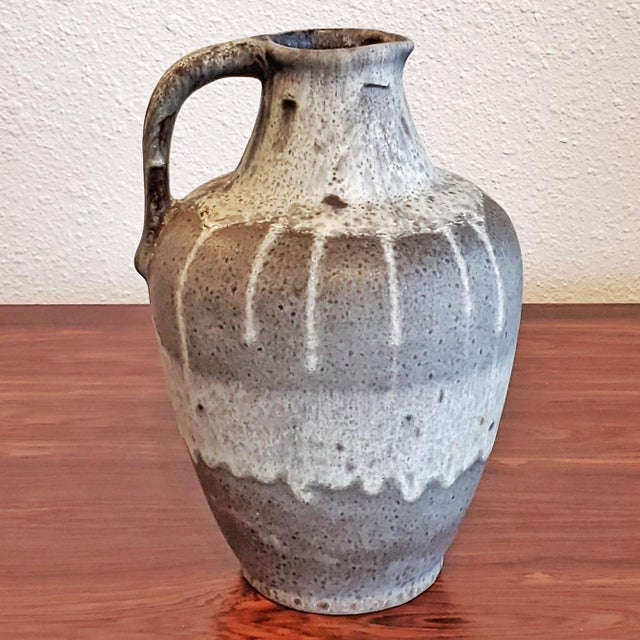 A gorgeous gray and white flowing fat lava glaze on a beautifully formed jug vase designed by Hans Kraemer for ES Keramik....
