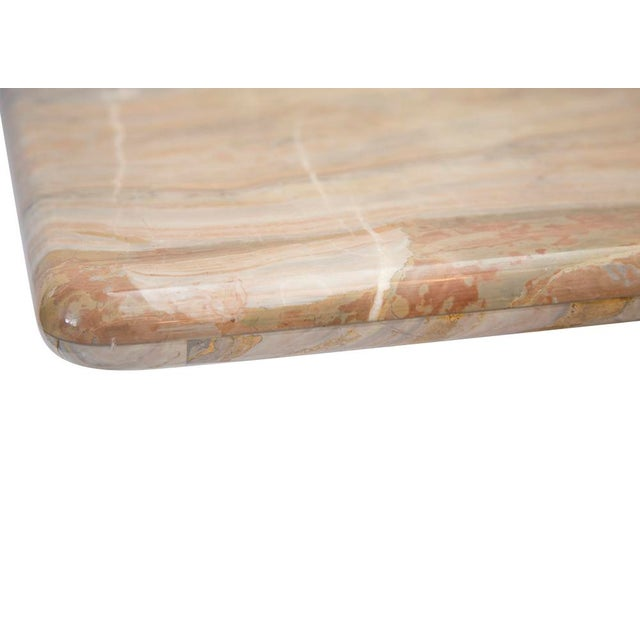 A gorgeous, highly variegated marble console table featuring veining in gray, sand and salmon with a highly polished...