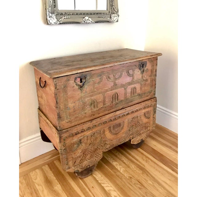 What an incredible statement piece! This antique trunk on wheels has stunning carvings on the front and sides with...