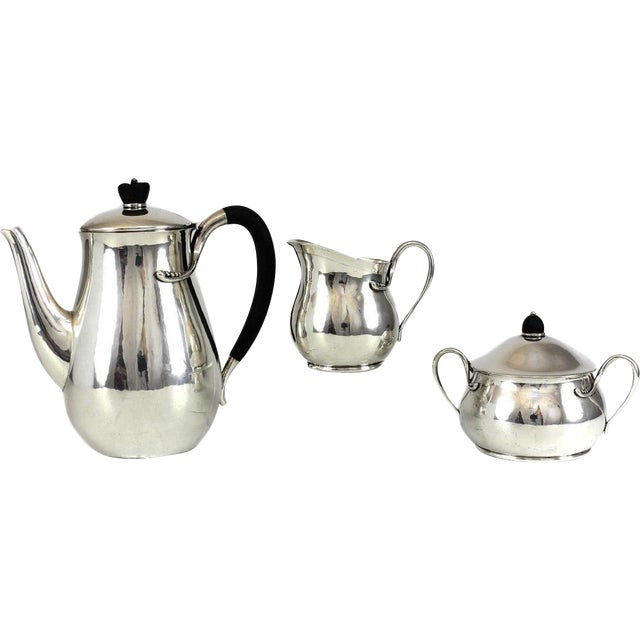 A stunning 3 piece Evald Nielsen silver modernist coffee service set, circa 1940. The coffee pot and creamer have black...