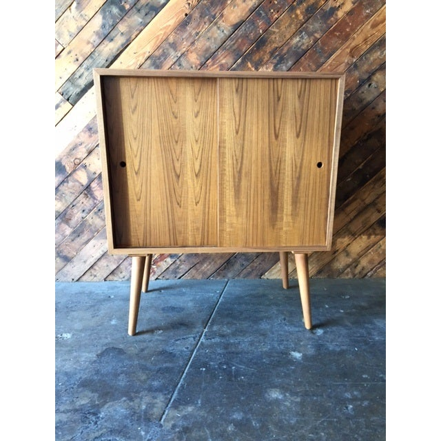 Handmade in Los Angeles, this is a custom-built Mid-Century-style bar or record cabinet. The teak wood shows book-matched...