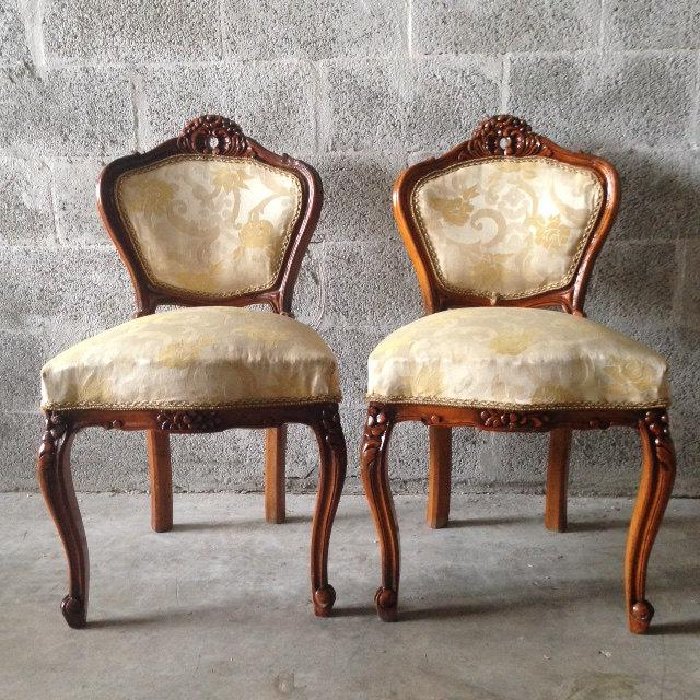 Beautifull combination of dark brown wood frame and French material used for the upholstery. The two chairs are sitting...