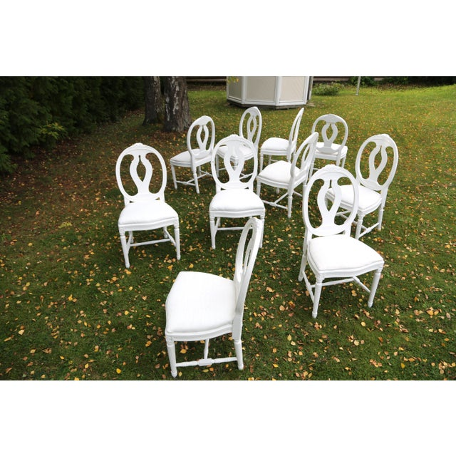 We have a set of 16 Gustavian style dining chairs with oval backs circa 1900 in white paint. The model is called Svenska...