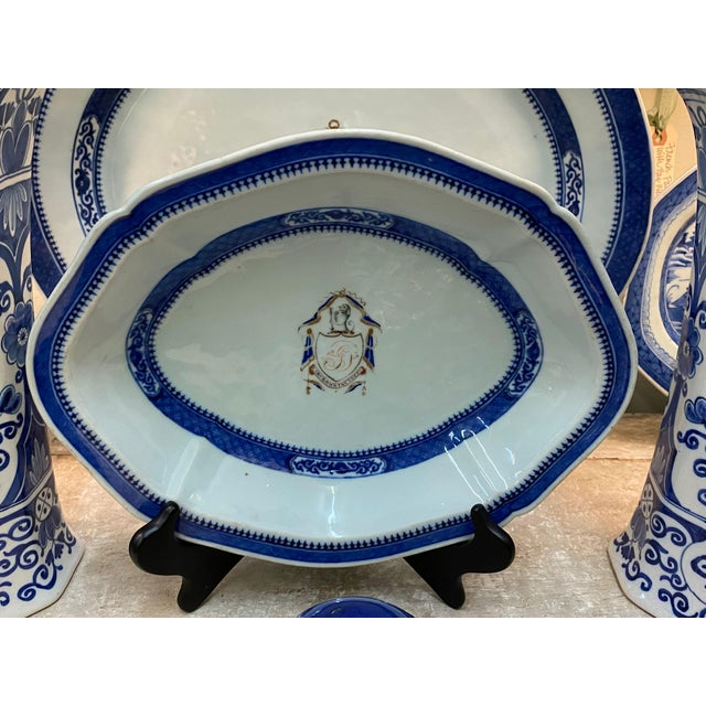 Chinese export armorial platter with a lion and shield crest that reads Labor Omnia Vincit. Crest with a dog holding a...