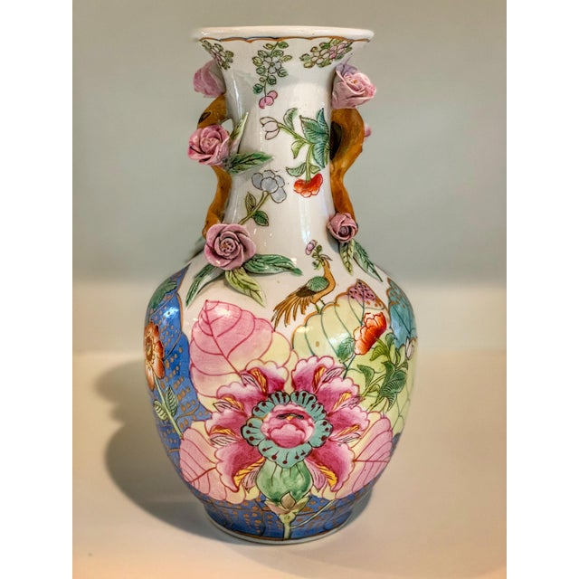 A late 19th century Chinese export tobacco leaf vase. With an enamel painted surface of flowers, birds, and brightly...
