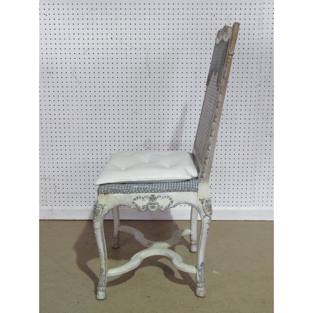 Swedish Rococo style distressed painted desk chair with a caned back.