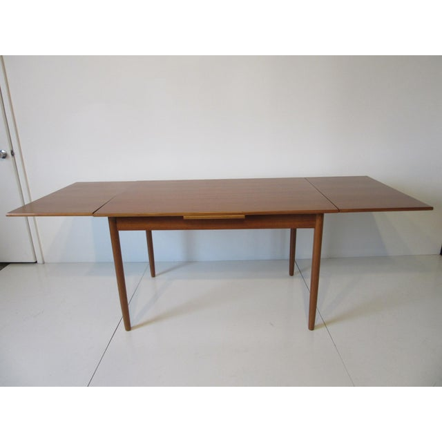 A teak wood extendable dining table with pull out leaves to both ends, manufactured by L & F Mobler Denmark . The...