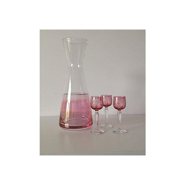 Late 1960's; Czechoslovakian hand blown, slanted glass wine carafe, cranberry and clear coloration with 22k. Gold rimmed...