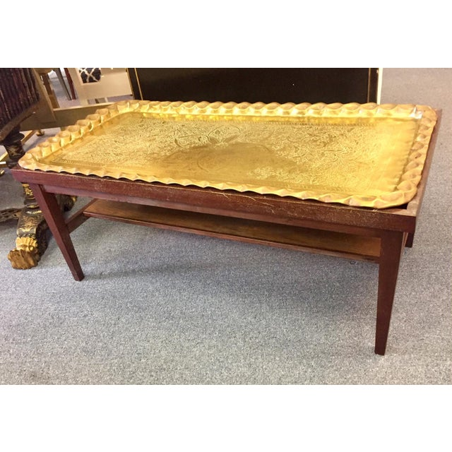 Gorgeous wood coffee table with hand-etched and hammered brass tray top. Slender shelf below. Tapered table legs.