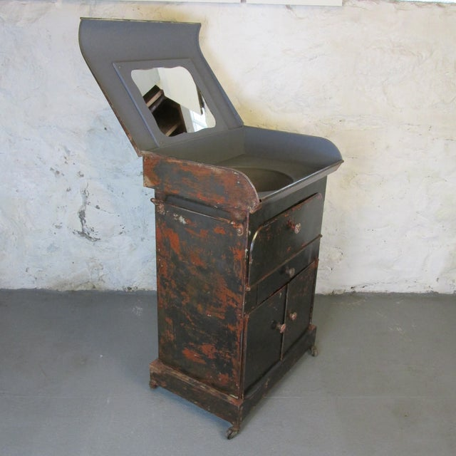 Antique (circa 1910) riveted steel Campaign Style vanity and washbasin. Features single drawer, drop-down door with...