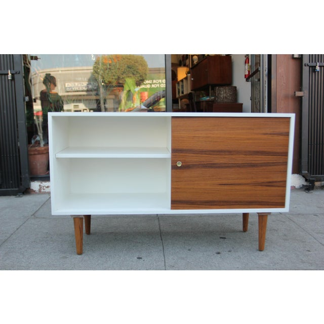 Great looking white lacquered and wood credenza. The doors and legs are made out of teak and rest of the body has been...