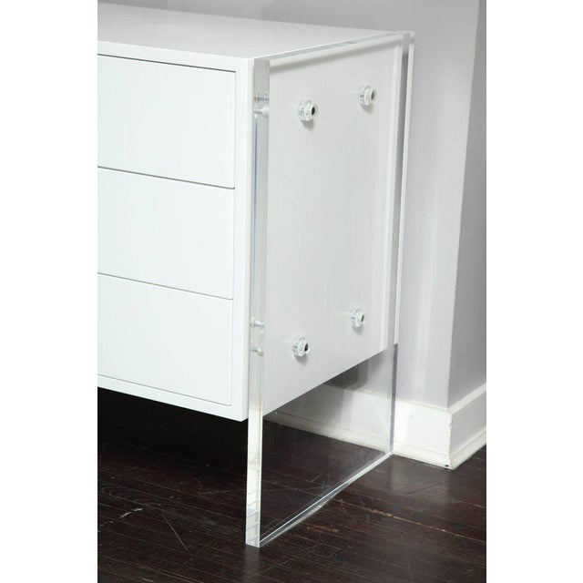 Six-drawer white lacquer dresser with acrylic side panels.