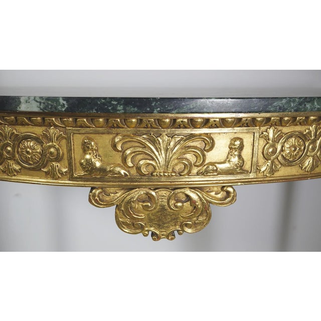 Elegant demilune console table. Classic green marble top and intricately carved, gilt wood base. Perfect for an entry or a...