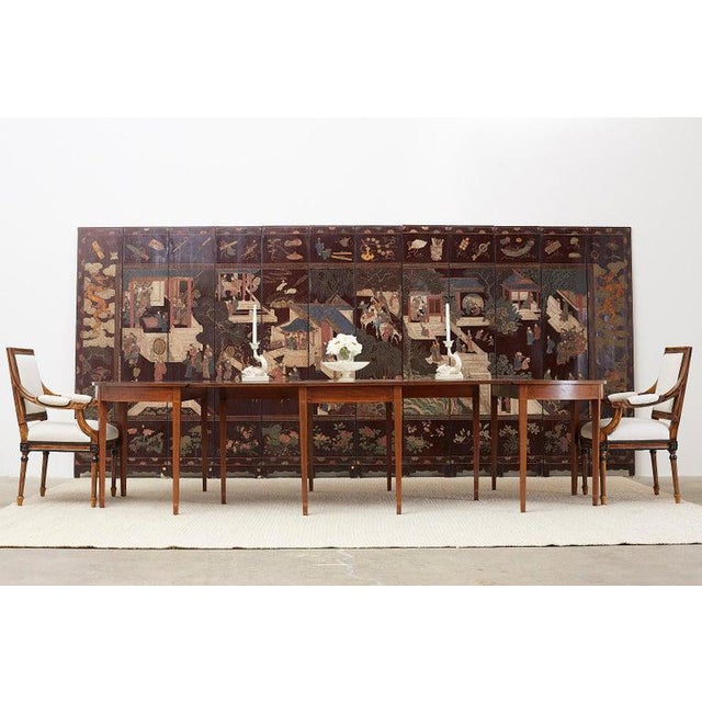 Grand American Hepplewhite or Federal style three-part mahogany and fruitwood inlaid banquet dining table. Comprised of a...