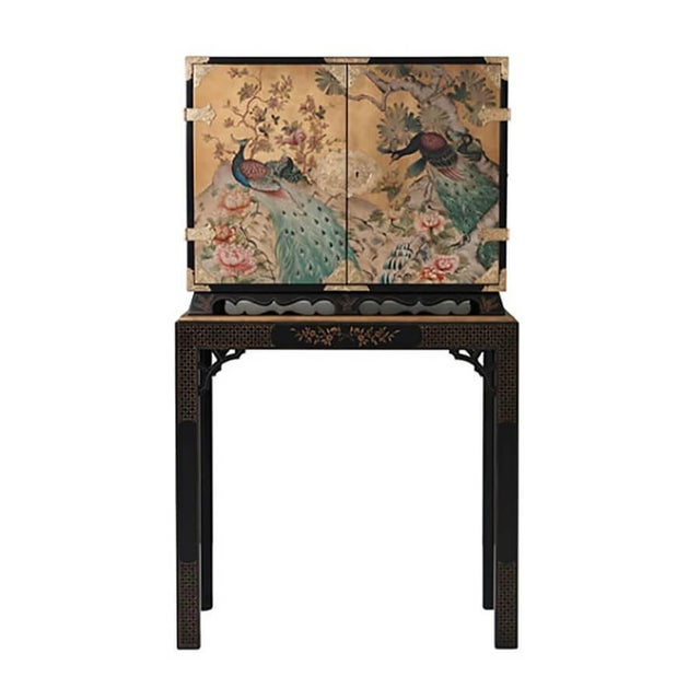 A finely hand painted and black lacquered cabinet on stand, the cabinet with gold leaf and hand-painted decoration of...