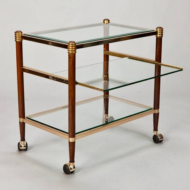 Circa 1970s three tier Italian serving or trolley table with brass frame, glass surfaces and polished wood legs with brass...