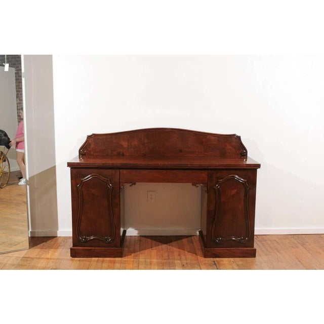 19th century sideboard of mahogany in the style of William IV. The sideboard has a thick mahogany top holding a wide...