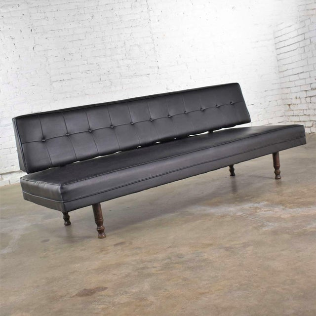 Handsome mid-century modern settee or loveseat sofa in black vinyl faux leather by Universal of High Point. It is in...